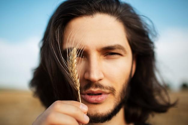 Ritratto del primo piano di giovane uomo bello con i capelli lunghi. tenendo il picco di grano.