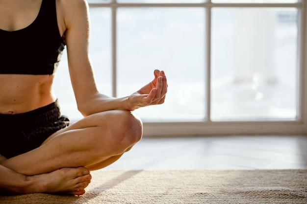 Close up ritratto di giovane donna in buona salute seduto nella posizione del loto e meditando.
