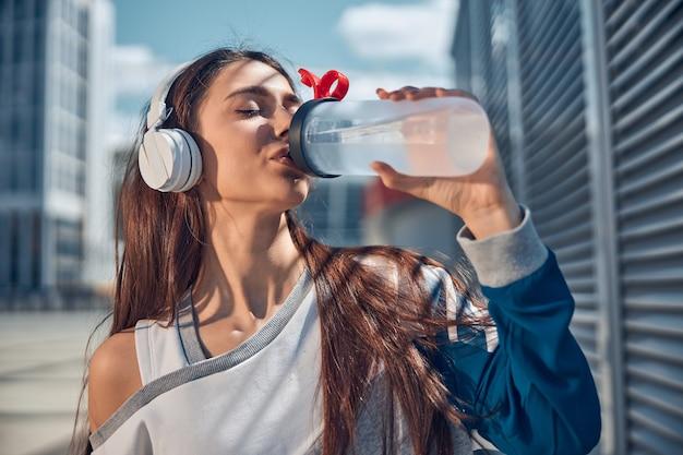 Ritratto ravvicinato di una giovane donna alla moda dai capelli lunghi che beve acqua con gli occhi chiusi all'aperto