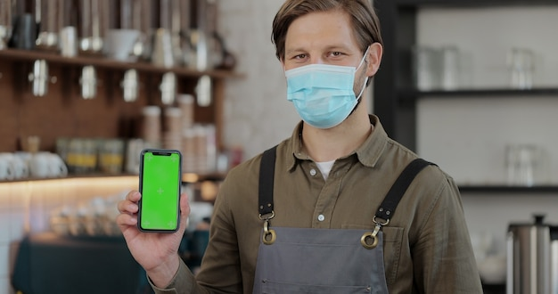Primo piano ritratto di un giovane barista in maschera facciale in piedi davanti al bancone del bar e che mostra lo schermo verde dello smartphone alla fotocamera tenendo la mano destra nella caffetteria.