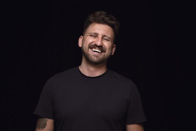 Close up ritratto di giovane uomo isolato sul muro nero. vere emozioni del modello maschile. piangere ridendo e sorridendo. espressione facciale, concetto di emozioni umane.