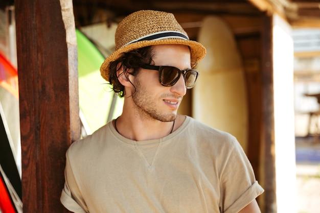 Close up ritratto di un giovane uomo in occhiali da sole e cappello in piedi presso la capanna di surf