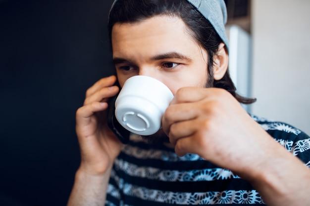 Chiuda sul ritratto di giovane uomo che parla sul suo smartphone e beve caffè dalla tazza di ceramica.