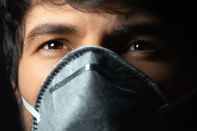 Close up ritratto di giovane uomo che indossa la maschera facciale respiratoria su sfondo nero.
