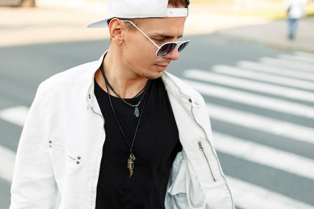 Close up ritratto di un giovane uomo in una giacca bianca con un berretto da baseball bianco e occhiali da sole sulla strada