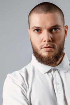Close-up ritratto di giovane uomo in una maglietta bianca sul serio sul grigio