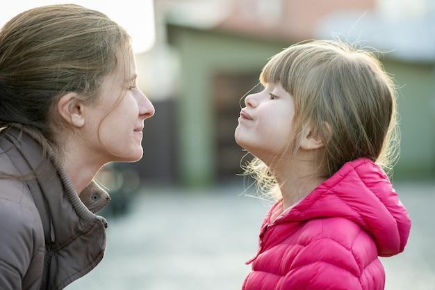 Chiuda sul ritratto di giovane mamma e di sua figlia che fanno l'un l'altro i fronti all'aperto