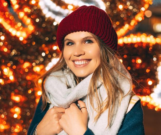 Primo piano ritratto di una giovane ragazza carina che indossa abiti invernali con luci di natale come sfondo.