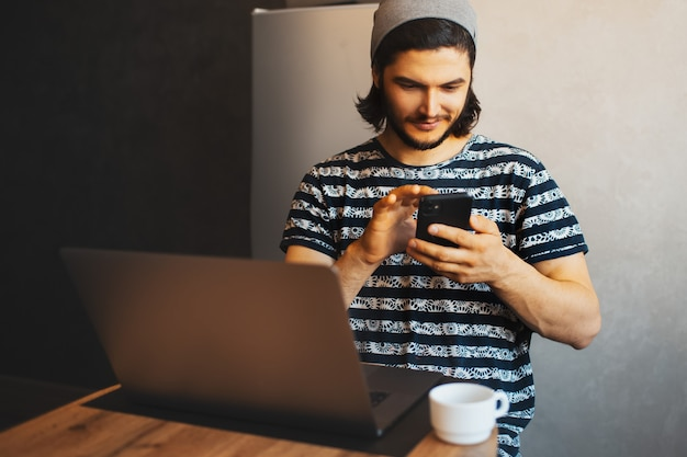 Ritratto del primo piano di giovane uomo sorridente che per mezzo dello smartphone; laptop e tazza di caffè sul tavolo di legno.