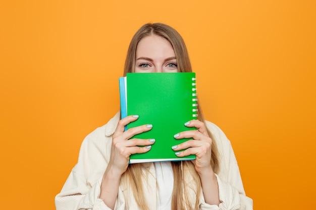 Close up ritratto di una giovane studentessa in una giacca beige copre il viso con un quaderno verde isolato sopra la parete arancione