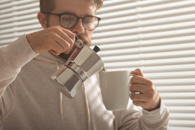 Ritratto del primo piano di giovane uomo alla moda hipster versando il caffè in ufficio il giorno d'estate. concetto di tonificante mattina e stato d'animo positivo