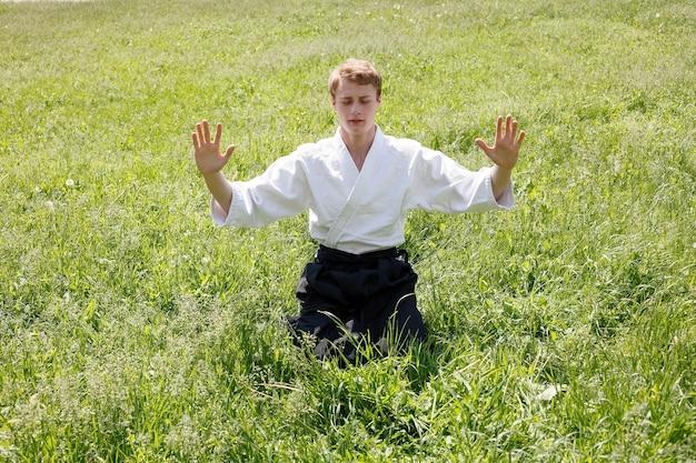 Close up ritratto di giovane uomo taekwondo esercizio presso il parco naturale