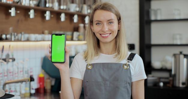 Primo piano ritratto di una giovane donna barista in piedi davanti al bancone del bar e che mostra lo schermo verde dello smartphone alla telecamera tenendo la mano destra nella caffetteria. concetto di affari.