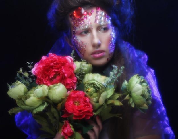 Primo piano ritratto di giovane donna in un'immagine creativa con grandi fiori.
