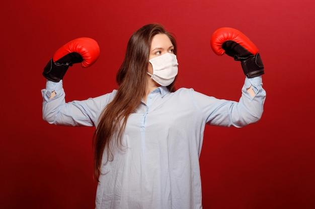 Ritratto di close-up di giovane donna in guantoni da boxe rossi su sfondo rosso in maschera protettiva medica, pandemia di coronavirus, lotta con virus