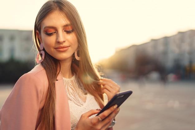 Chiuda sul ritratto di una giovane donna che parla sul suo telefono nella via