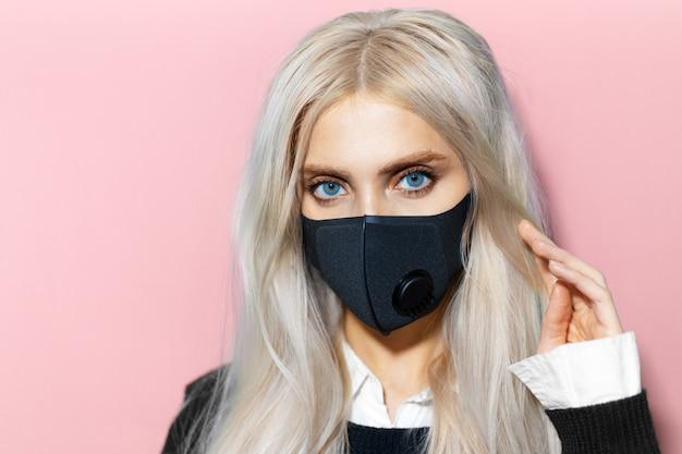 Ritratto ravvicinato di una giovane donna che indossa una maschera respiratoria contro il coronavirus su sfondo di colore rosa pastello.