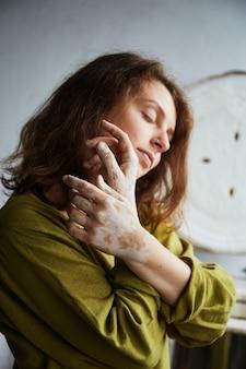 Close up ritratto di ceramista e le sue mani sporche di argilla. studio di ceramica il processo di creazione della ceramica. la maestra ceramista lavora nel suo studio