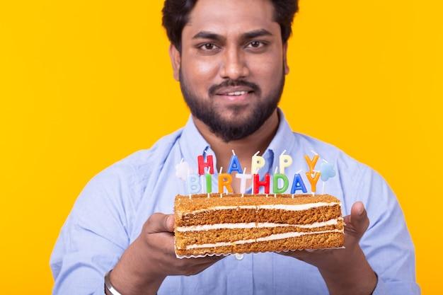 Primo piano del giovane positivo che tiene una torta di buon compleanno e due luci brucianti del bengala che posano sopra