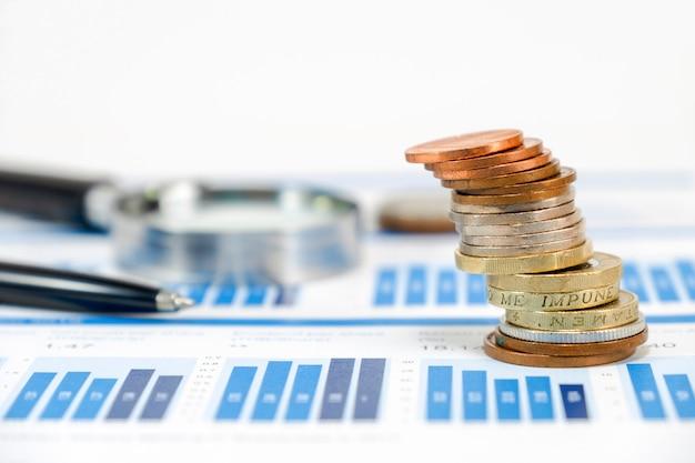 Chiuda sulle monete di sterlina che impilano sul grafico capitale con il vetro della lente e della penna Foto Premium