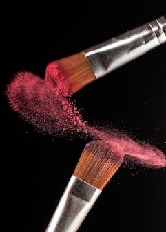 Chiuda in su spruzzi di polvere e pennello per truccatore o blogger di bellezza in sfondo nero
