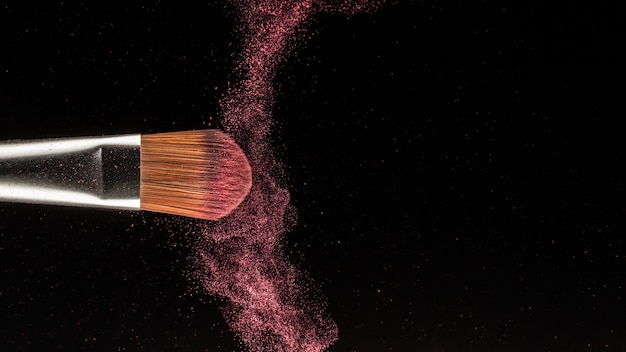 Chiuda sulla spruzzata della polvere e spazzoli per il truccatore o il blogger di bellezza nel fondo nero