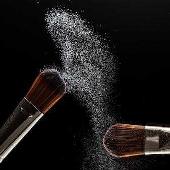 Chiuda sulla spruzzata della polvere e spazzoli per il truccatore o il blogger di bellezza