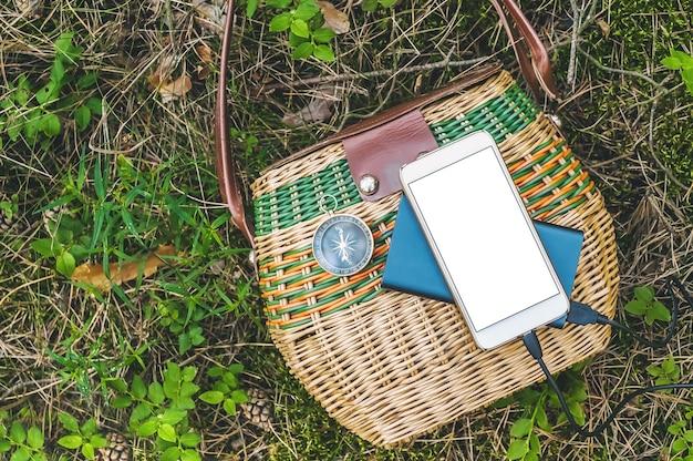 Primo piano, powerbank con smartphone mockup su un cesto nella foresta. concetto di viaggio.