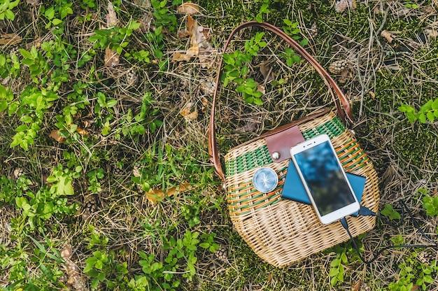 Primo piano, powerbank con smartphone su un cesto nella foresta. concetto di viaggio.