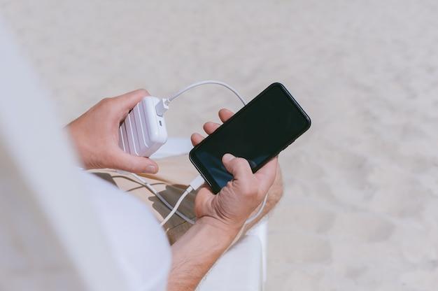 Primo piano di un powerbank con uno smartphone in carica nelle mani di un ragazzo sulla spiaggia. sullo sfondo di sabbia.