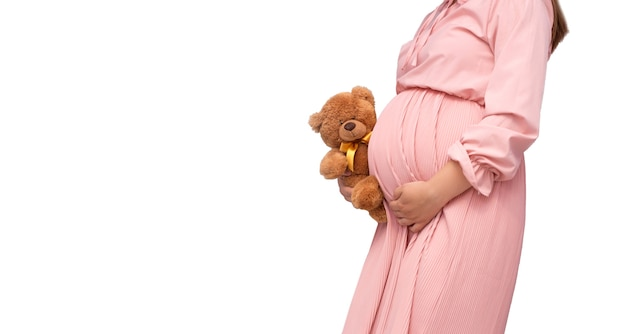 Chiuda in su della pancia della donna incinta con il giocattolo dell'orsacchiotto