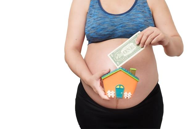 Primo piano di donna incinta, mano che tiene la casa forma salvadanaio e banconota dollaro