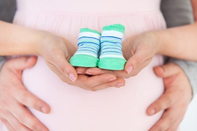 Primo piano di una donna incinta che tiene i pattini di bambino e di suo marito