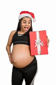 Primo piano della donna incinta che tiene un contenitore di regalo di natale. concetto di gravidanza, natale e aspettativa.