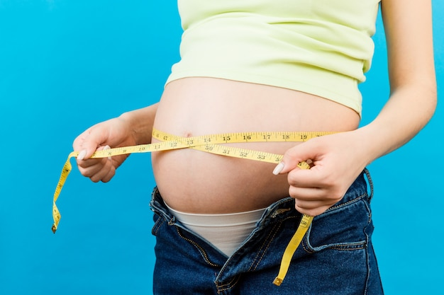 Chiuda su della donna incinta che usando la misura di nastro per controllare lo sviluppo del bambino e la crescita della pancia. misura in pollici