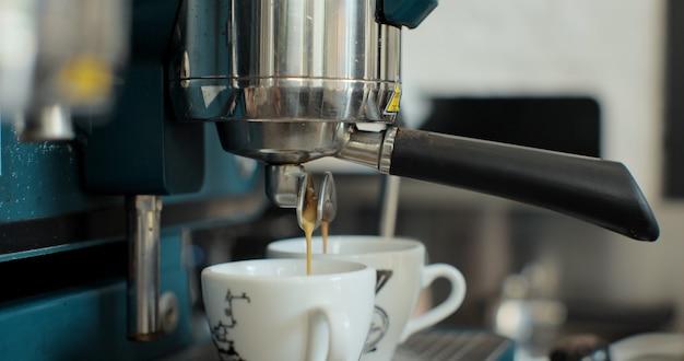 Chiuda in su preparare doppio colpo di caffè espresso, rallentatore. barista che prepara un caffè espresso in un bar.