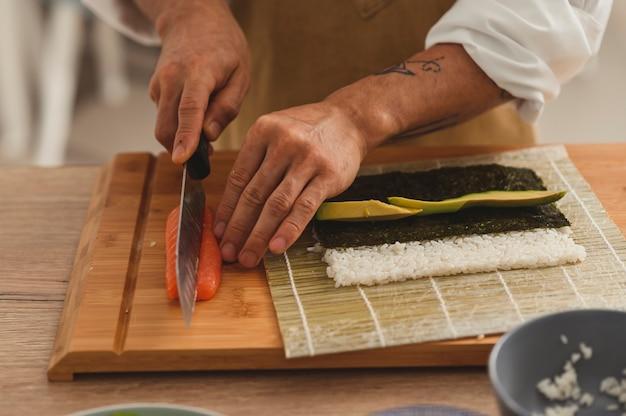 Close up preparazione rotolo sushi a casa mani maschili affettare ingredienti salmone cetriolo avocado e