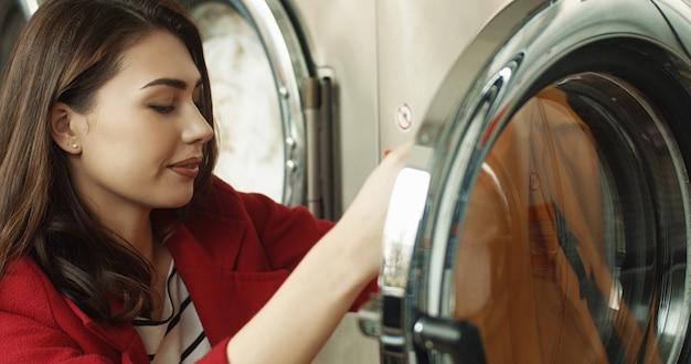 Chiuda in su della donna abbastanza caucasica che elimina i vestiti puliti dalla lavatrice. ragazza attraente lavare i vestiti in camera di servizio lavanderia.