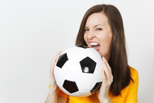 Close up abbastanza europeo giovane donna felice sorridente, tifoso o giocatore in uniforme gialla che morde il pallone da calcio isolato su sfondo bianco. sport, giocare a calcio, salute, concetto di stile di vita sano.