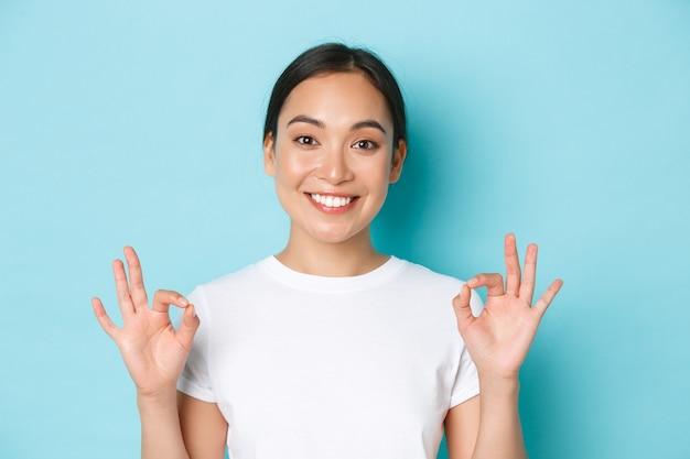 Primo piano della ragazza asiatica sorridente abbastanza soddisfatta in maglietta bianca, mostrando il gesto di raccomandazione, segno ok e annuire in approvazione, scelta di complimenti, d'accordo con te, muro azzurro in piedi