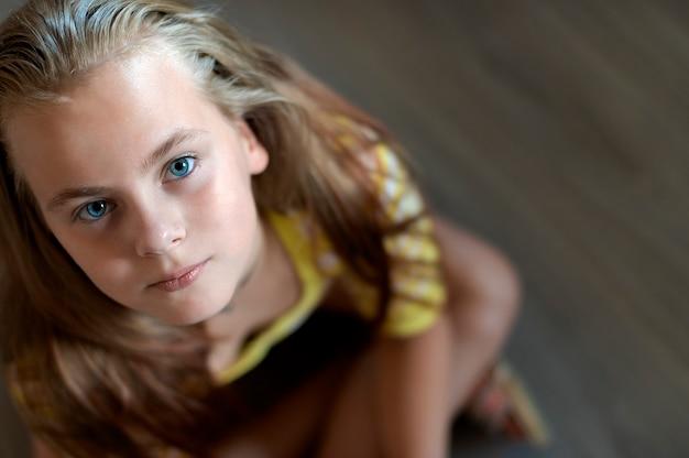 Primo piano del viso di una bella ragazza adolescente con gli occhi azzurri che guarda l'obbiettivo