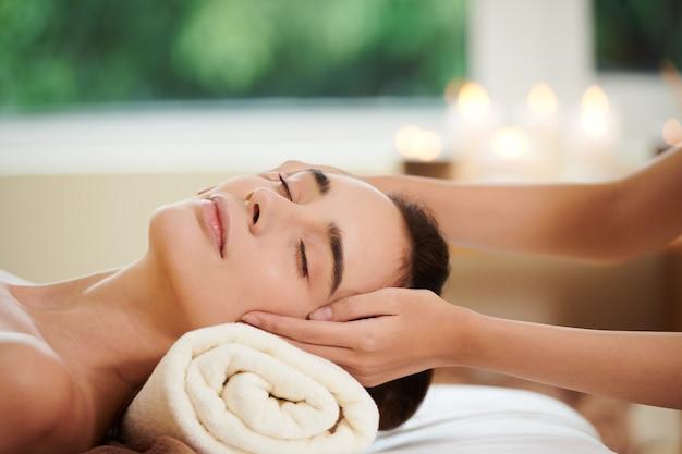 Primo piano di una bella donna sdraiata sul letto e che riceve un massaggio dal terapista