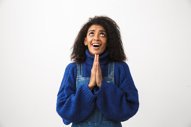Primo piano di una bella giovane donna africana che indossa un maglione in piedi isolato, pregando
