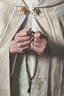 Primo piano del sacerdote in abbigliamento formale che tiene i grani del rosario