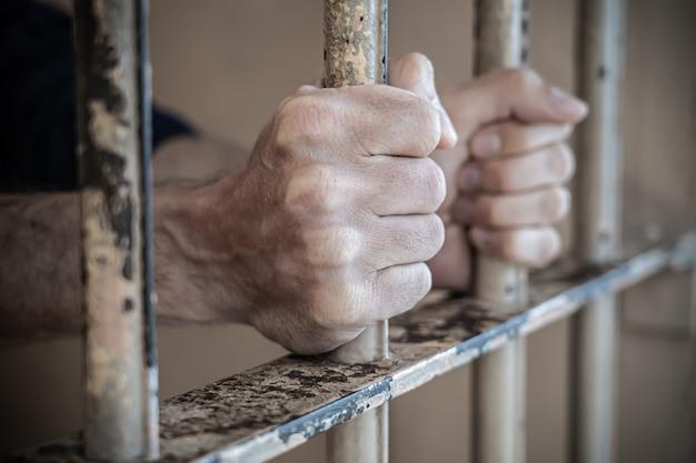 Chiuda in su delle mani del prigioniero in prigione