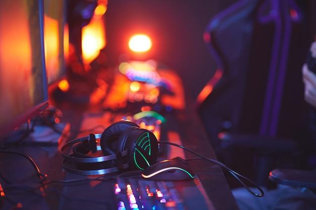 Close up pro-gaming attrezzature sulla scrivania del computer, concentrarsi sulle cuffie illuminate, copia dello spazio