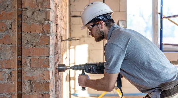 Primo piano del processo di perforazione di un muro di mattoni in un cantiere edile.