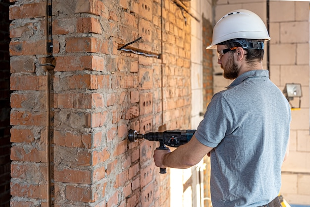 Primo piano del processo di perforazione di un muro di mattoni in un cantiere edile