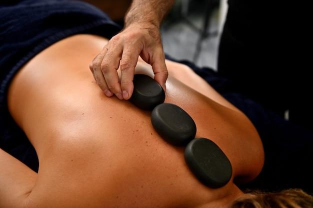 Primo piano del massaggiatore prodessional che posa pietre calde lungo la spina dorsale della giovane donna. massaggio ayurvedico con pietre calde nel moderno salone spa