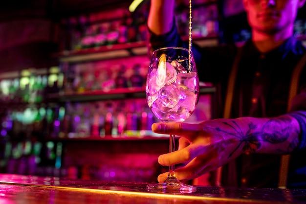 Primo piano del barman professionista che finisce la preparazione di cocktail alcolici in luce al neon multicolore, lo dà al cliente. intrattenimento, bevande, concetto di servizio. bar moderno, colori neon alla moda.
